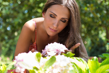 Young beautiful girl smells flowers, against green summer garden