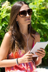 Young beautiful girl listening to music with digital tablet.