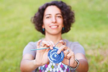 Happy smiling woman making crochet potholder outdoors