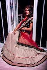 Indian bride  sitting in black, beige, red sari