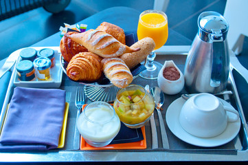Continental breakfast with croissant, jam, coffee and orange jui