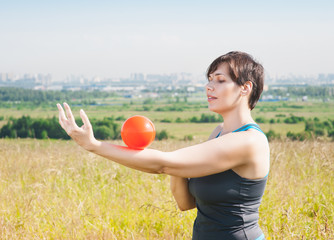 Beautiful plus size woman exercising with ball