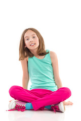 Girl sitting on the floor with legs crossed.