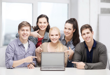 smiling students pointing to blank lapotop screen