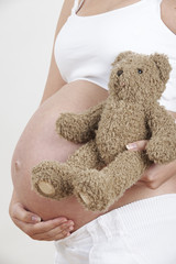 Close Up Of Pregnant Woman Holding Teddy Bear