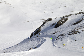 Snowboarders and skiers on groomed slope