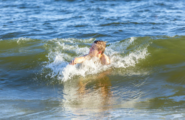 boy enjoys swimming in the waves