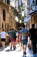 Tourists walking on Dubrovnik Old City street in evening light