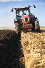 Farmer plowing stubble field with red tractor