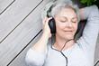 Leinwanddruck Bild - Seniorin mit Kopfhörern genießt Musik