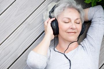 Seniorin mit Kopfhörern genießt Musik
