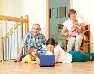Happy multigeneration family together laptop at home