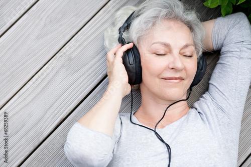 Seniorin mit Kopfhörern genießt Musik - 68259389