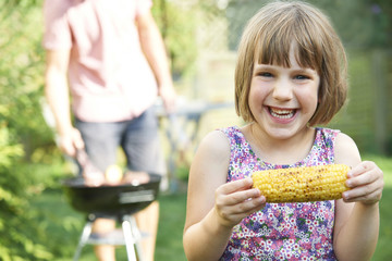 Young Girl Eating Sweetcorn At Family Barbeque