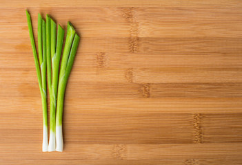 Spring green onion on wooden board