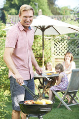 Father Cooking Barbeque For Family In Garden At Home