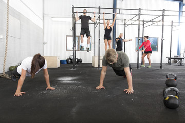 Workout group trains exercises at fitness gym