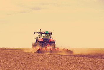 Red tractor driven by farmer cultivating land at spring