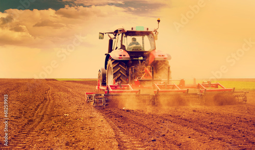 Farmer in tractor preparing land for sowing - 68259903