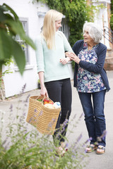 Teenage Girl Helping Senior Woman To Carry Shopping