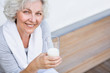 Leinwandbild Motiv Seniorin mit einem Glas Milch