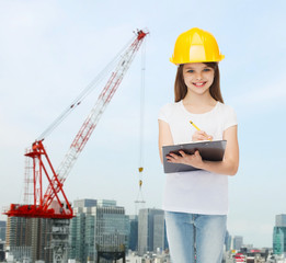 smiling little girl in hardhat with clipboard