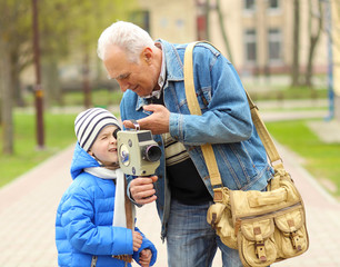 Grandfather teaches his grandson to photograph