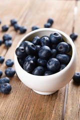 Delicious blueberries in bowl on table close-up