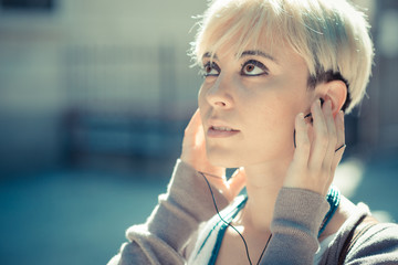 beautiful young blonde short hair hipster woman listening music