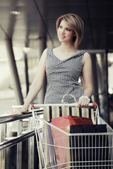 Young fashion woman with shopping cart in the mall