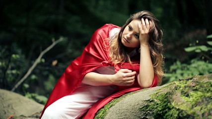 Sad beautiful woman, red riding hood sitting in the forest
