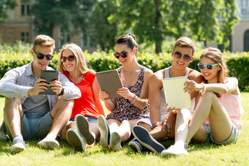 smiling friends with tablet pc computers in park