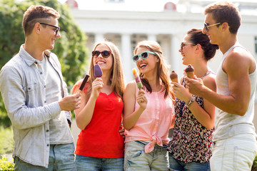 group of smiling friends with ice cream outdoors