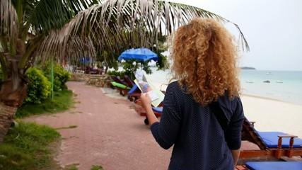 Woman Looking Beach Bungalow or Beach Resort.