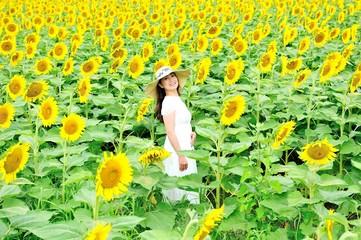 ひまわり畑に立っている白いワンピースと麦わら帽子を着ているアジア人の美しい女性