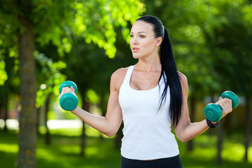 woman in fitness wear exercising with dumbbell, outdoors