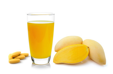 mango juice in a glass and vitamin c tablet on white background