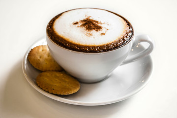 Coffee cup and cracker on white table with reflect in cafe