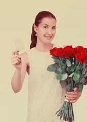 Girl with bouquet of red roses and card in hand.