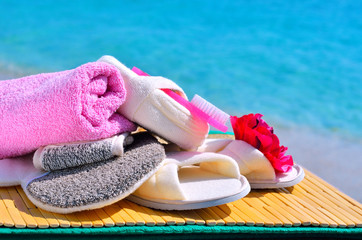 Natural bath sponges, bath slippers, pumice and towel against bl