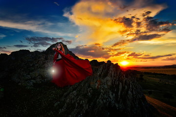 beautiful woman with red cloak in the sunset light