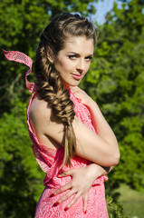 beautiful young woman wearing pink dress posing in green forest.