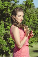 beautiful romantic woman wearing pink dress posing in green fore