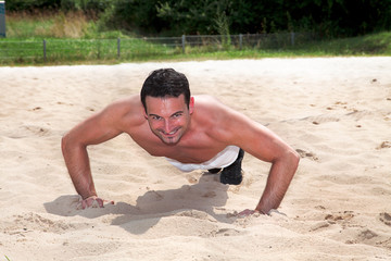 Sportlicher Mann macht Liegestützen am Strand