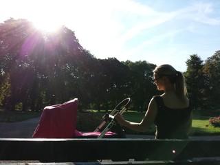 Junge Mutter mit Kinderwagen auf Parkbank