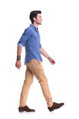 side view of a smiling young casual man walking
