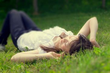 芝生で仰向けで寝る女性