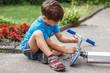 Little boy repairing scooter