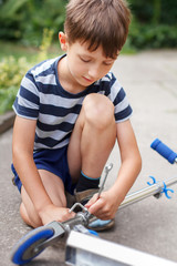 Little caucasian boy repairing scooter