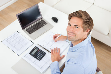 Businessman Calculating Tax At Desk